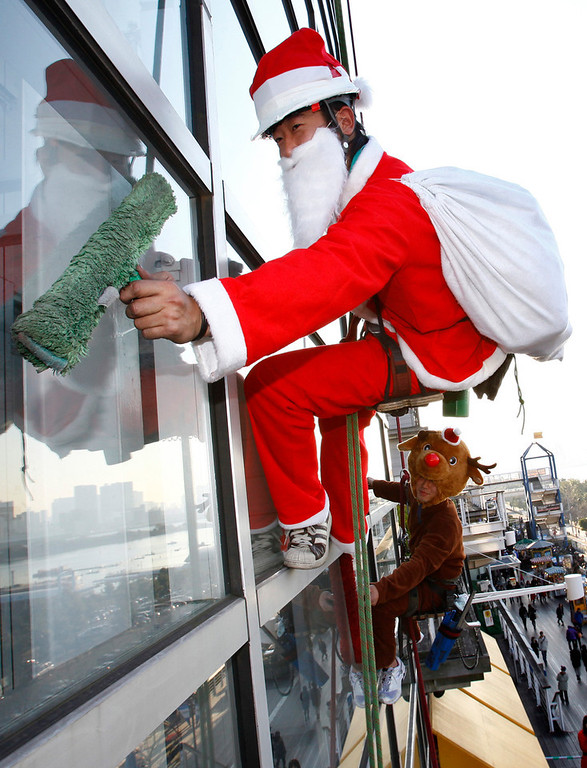 Description of . Junya Kono, left, and Tomoharu Fujimaki, window cleaner dressed as Santa Claus and reindeer clean a window at a shopping mall in Tokyo, Japan, Wednesday, Dec. 23, 2009. (AP Photo/Shizuo Kambayashi)