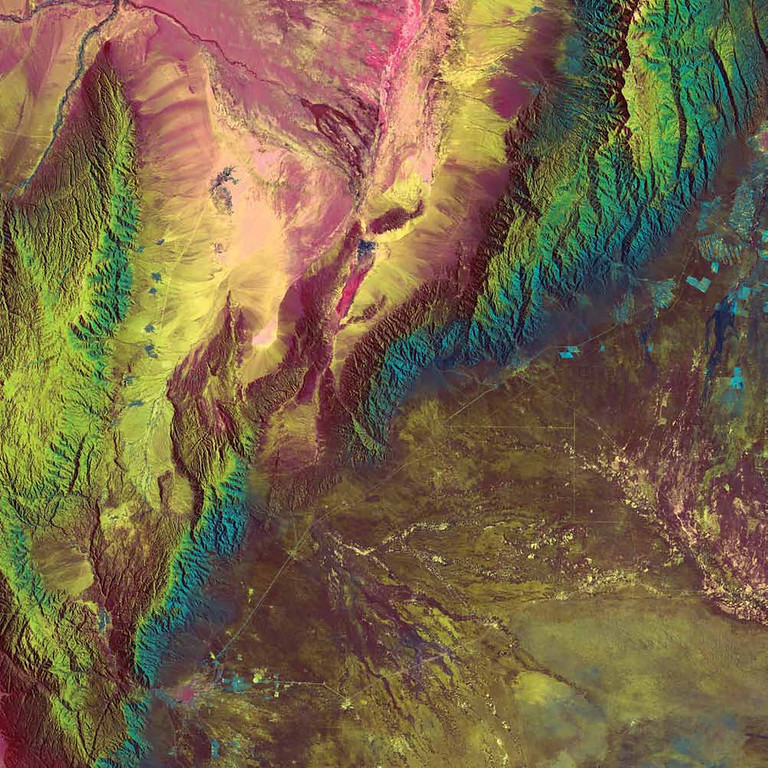 Description of . La Rioja, Argentina In this 1985 Landsat 5 image, a myriad of colors denote the composition and textures of the Sierra de Velasco Mountains of northern Argentina. Pink tones and warm hues indicate the drier, more barren areas of the mountains. Ribbons of blues and greens hint at the moister areas of vegetation and heavy growth. At the base of the mountains in the lower left, a pink area marks the city of La Rioja, which is the capital city of one of the least populated and most arid provinces of Argentina. In stark contrast, the upper right of the image shows the lusher surroundings of the city of San Fernando del Valle de Catamarca and extensive vineyards.   NASA