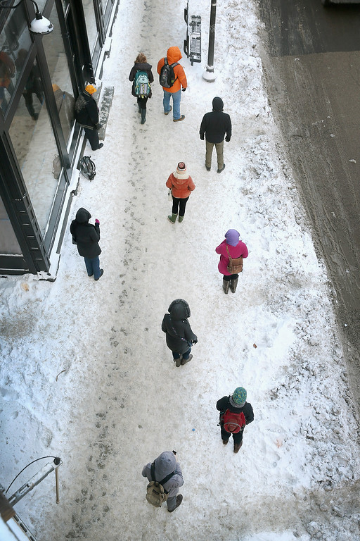 Description of . Commuters wait on a frozen sidewalk in below zero temperatures for a bus to arrive on January 7, 2014 in Chicago, Illinois. Chicago is experiencing its third consecutive day of below zero temperatures.  (Photo by Scott Olson/Getty Images)