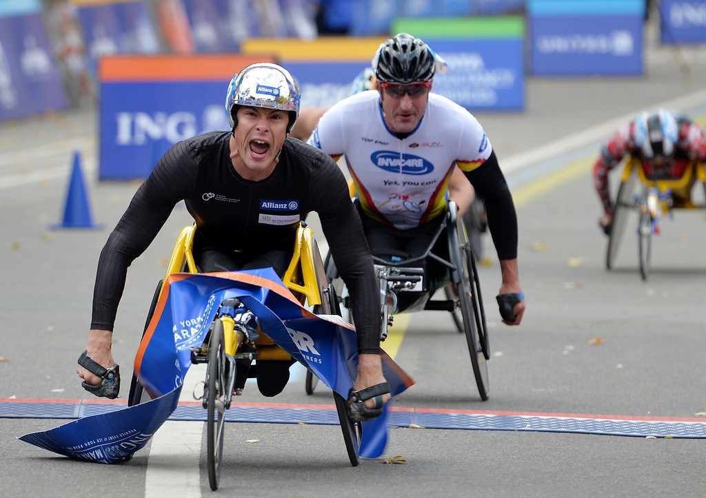 Description of . Marcel Hug of Switzerland (L) crosses the finish line to win the Men's Wheelchair Division of the New York City Marathon on November 3, 2013 in New York. Ernst Van Dyk (C) of South Africa finishes second.    STAN HONDA/AFP/Getty Images