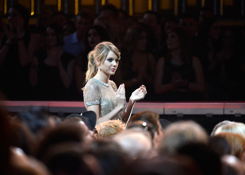 Description of . Singer Taylor Swift stands in the audience during the 56th GRAMMY Awards at Staples Center on January 26, 2014 in Los Angeles, California.  (Photo by Kevork Djansezian/Getty Images)