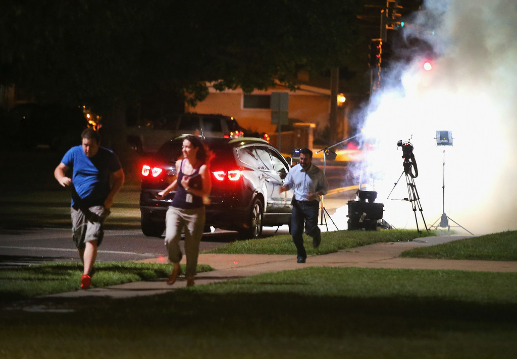 Description of . An Al Jazeera television crew, covering demonstrators protesting the shooting death of teenager Michael Brown, scramble for cover as police fire tear gas into their reporting position on August 13, 2014 in Ferguson, Missouri. Brown was shot and killed by a Ferguson police officer on Saturday. Ferguson, a St. Louis suburb, is experiencing its fourth day of violent protests since the killing.  (Photo by Scott Olson/Getty Images)