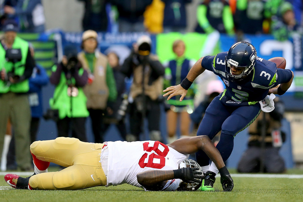 . Quarterback Russell Wilson #3 of the Seattle Seahawks fumbles the ball in the first quarter as he is tackled by outside linebacker Aldon Smith #99 of the San Francisco 49ers during the 2014 NFC Championship at CenturyLink Field on January 19, 2014 in Seattle, Washington.  (Photo by Ronald Martinez/Getty Images)