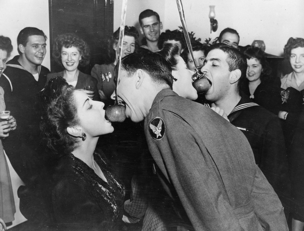 Description of . U.S. servicemen bob for apples with their USO hostess companions during a Hallowe'en party hosted by the tenants of a 14-story cooperative apartment building in Beekman Place in New York City, Nov. 1, 1943.  (AP Photo)
