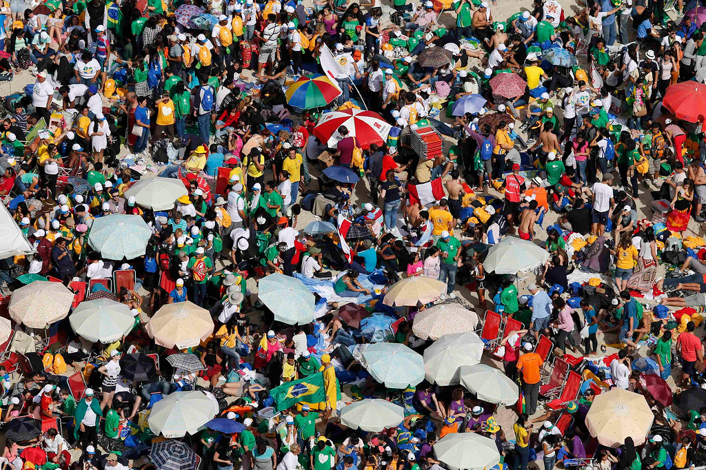 Description of . Catholic youths await the arrival of Pope Francis on Copacabana beach in Rio de Janeiro, July 26, 2013. Pope Francis on Thursday issued the first social manifesto of his young pontificate, telling slum dwellers in Brazil that the world's rich must do much more to wipe out vast inequalities between the haves and the have-nots. REUTERS/Sergio Moraes