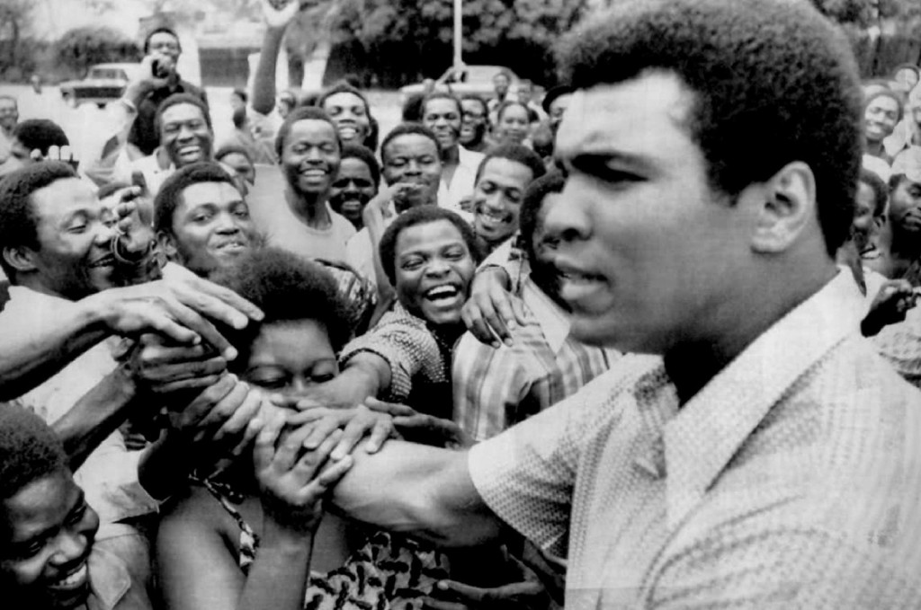 Description of . Zaire admirers grab the arm of Muhammad Ali when he stopped in downtown Kinshasa during his sightseeing tout Tuesday morning. 1974. Denver Post Library photo archive