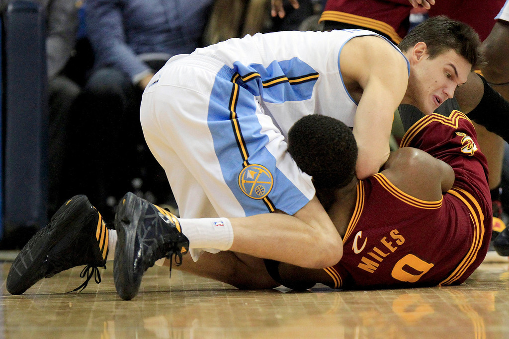 Description of . Denver Nuggets' Danilo Gallinari, top, and Cleveland Cavaliers' C.J. Miles, bottom, wrestle for a loose ball during the fourth quarter of an NBA basketball game Friday, Jan. 11, 2013, in Denver. The Nuggets won 98-91 (AP Photo/Barry Gutierrez)