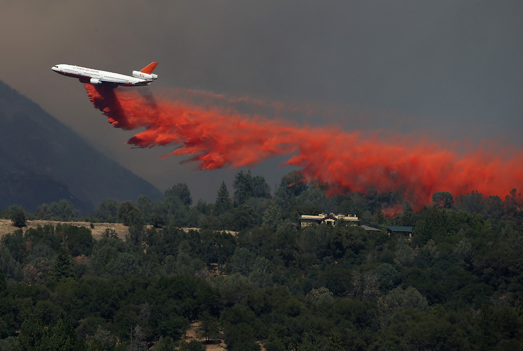 Description of . GROVELAND, CA - AUGUST 22:  A DC-10 air tanker drops fire retardant on a ridge ahead of the advancing Rim Fire on August 22, 2013 in Groveland, California. The Rim Fire continues to burn out of control and threatens 2,500 homes outside of Yosemite National Park. Over 1,000 firefighters are battling the blaze that was reduced to only 2 percent containment after it nearly tripled in size overnight.  (Photo by Justin Sullivan/Getty Images)