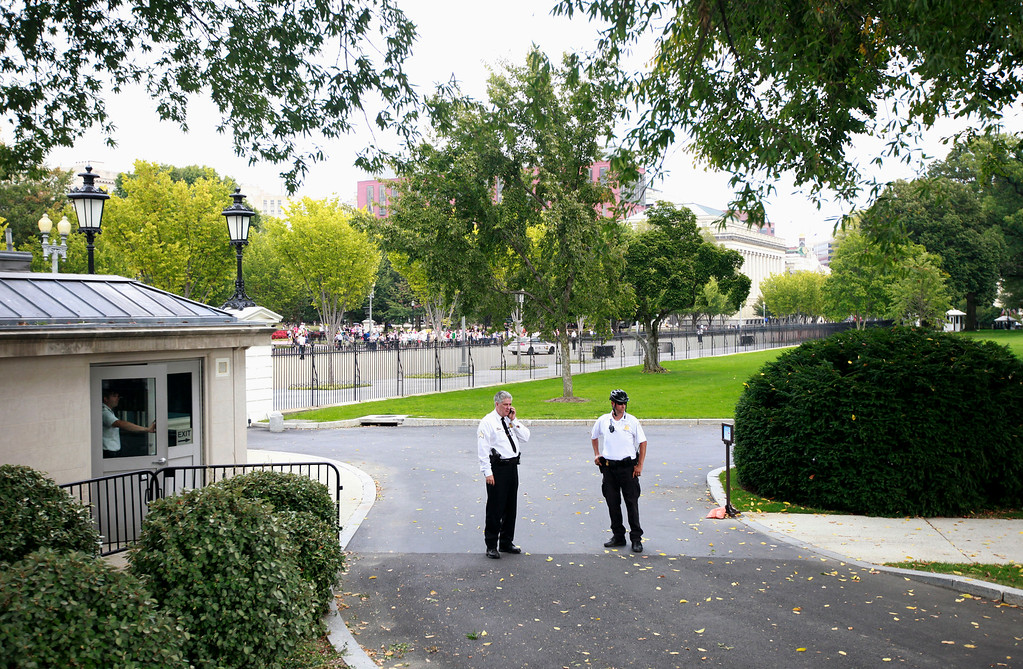 Description of . Members of the uniform division of the Secret Service stand in the driveway of the White House in Washington, Thursday, Oct. 3, 2013, as access to Pennsylvania Ave., was temporarily denied, after reports of shots on Capitol Hill. (AP Photo/Pablo Martinez Monsivais)