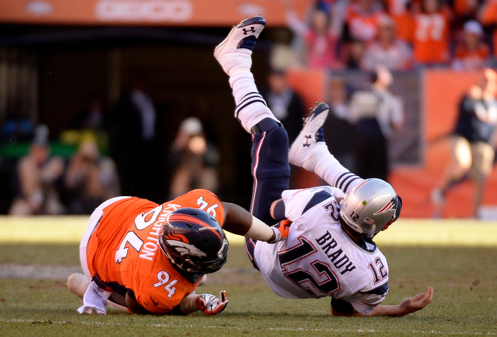 Description of . Denver Broncos defensive tackle Terrance Knighton (94) gets a hold of New England Patriots quarterback Tom Brady (12) for a sack during the third quarter. The Denver Broncos vs. The New England Patriots in an AFC Championship game  at Sports Authority Field at Mile High in Denver on January 19, 2014. (Photo by John Leyba/The Denver Post)