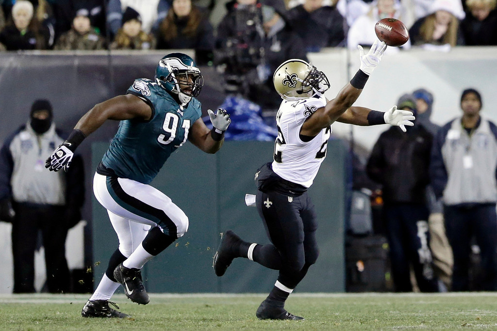 Description of . New Orleans Saints' Mark Ingram, right, cannot pull in a pass as Philadelphia Eagles' Fletcher Cox (91) pursues during the first half of an NFL wild-card playoff football game, Saturday, Jan. 4, 2014, in Philadelphia. (AP Photo/Julio Cortez)