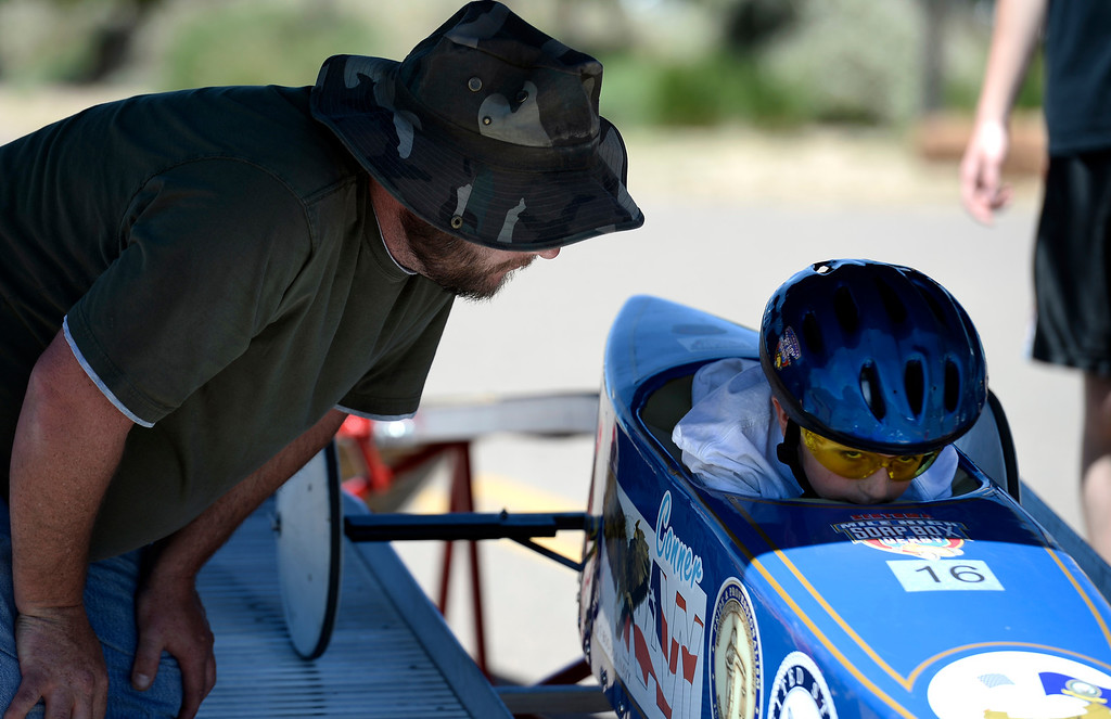 . Bob Stander gives a little pep talk to his son Conner Stander in car #16 during the Seventh Annual Sertoma Mile High Soap Box Derby June 9, 2013 in its first year at heir new location at Arapahoe County Fair Grounds. The Sertoma Club, a non-profit international organization helps many of the estimated 50 million Americans with speech and hearing disorders. (Photo By John Leyba/The Denver Post)