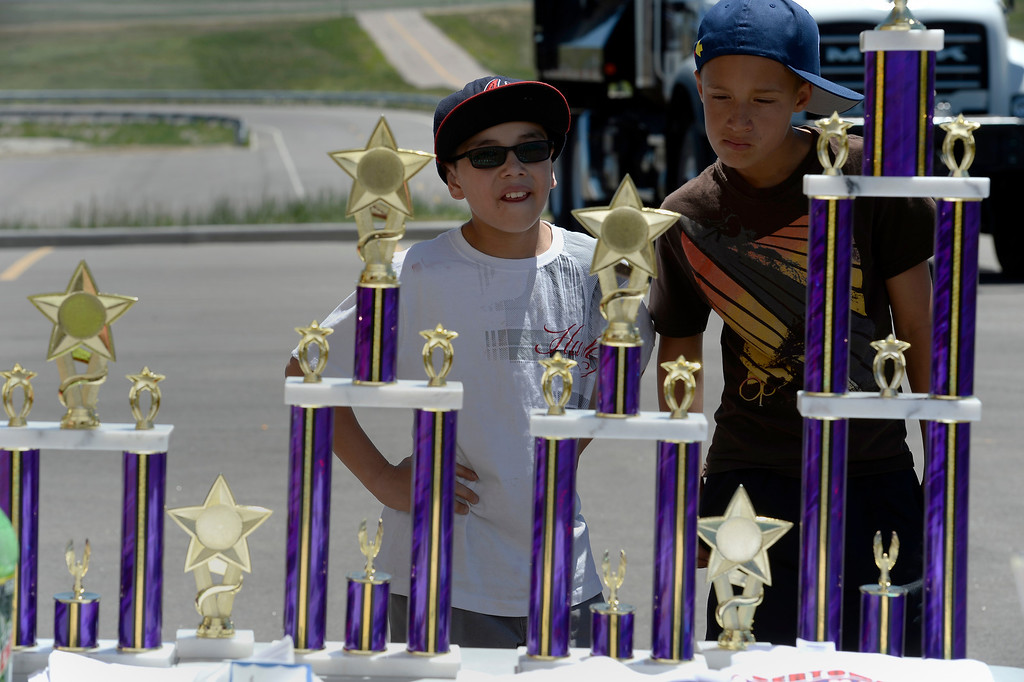 . Tristan Garcia (L) and Tristen Boggess check out the trophies at the Seventh Annual Sertoma Mile High Soap Box Derby June 9, 2013 in its first year at their new location at Arapahoe County Fair Grounds. The Sertoma Club, a non-profit international organization helps many of the estimated 50 million Americans with speech and hearing disorders. (Photo By John Leyba/The Denver Post)