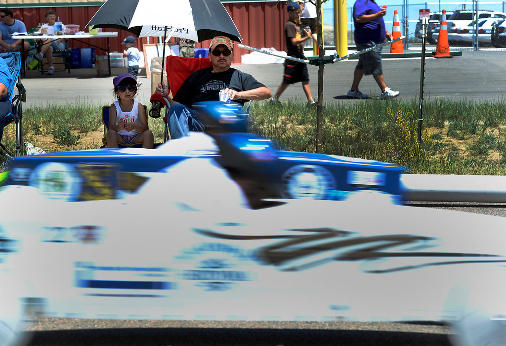 . Rueben Rios and Anayah Munsinger 5-years-old sit under the shade of an umbrella as they watch the races go by at the Seventh Annual Sertoma Mile High Soap Box Derby June 9, 2013 in its first year at their new location at Arapahoe County Fair Grounds. The Sertoma Club, a non-profit international organization helps many of the estimated 50 million Americans with speech and hearing disorders. (Photo By John Leyba/The Denver Post)