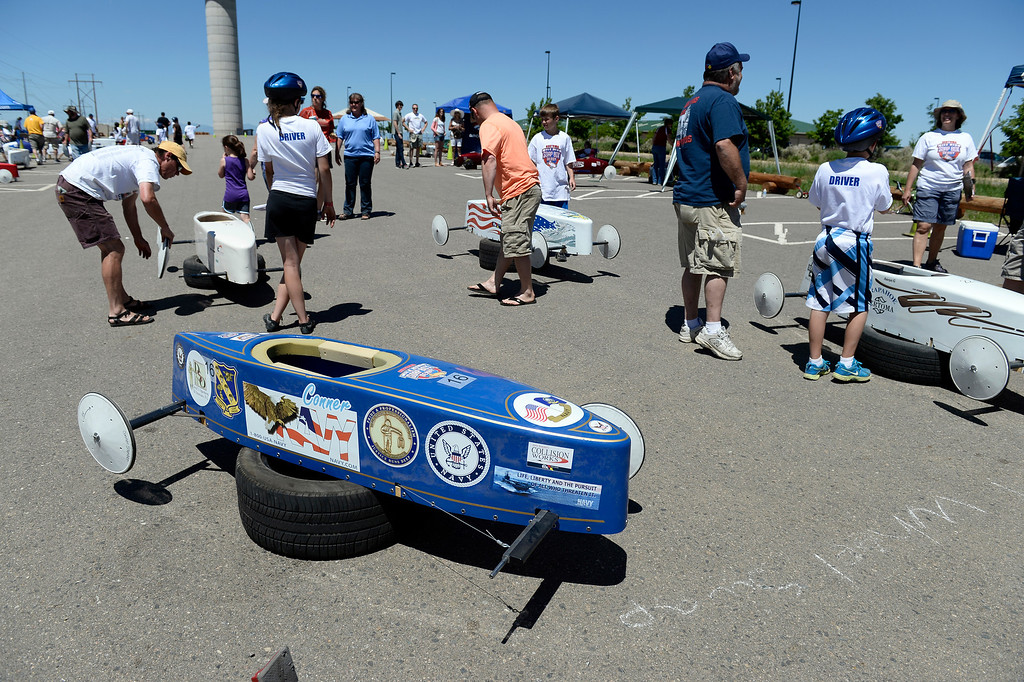 . Drivers swap out wheels at a station before their race during the Seventh Annual Sertoma Mile High Soap Box Derby. The Sertoma Club, a non-profit international organization helps many of the estimated 50 million Americans with speech and hearing disorders. (Photo By John Leyba/The Denver Post)