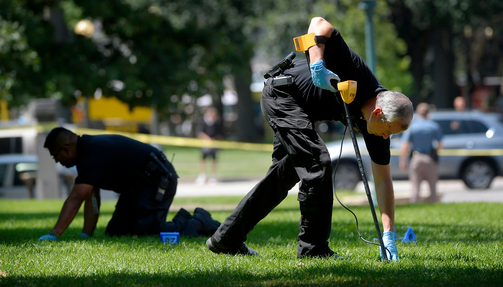 ". Authorities search Lincoln Park after a shooting on Colfax Avenue between Broadway and Lincoln Street near the Colorado Capitol Thursday morning in Denver, CO August 15, 2013. Three people are in custody and a gun has been recovered, no injuries were reported. Witnesses described the incident as a ""shootout\"" between two people, but police could not confirm that. (Photo By Craig F. Walker / The Denver Post)"