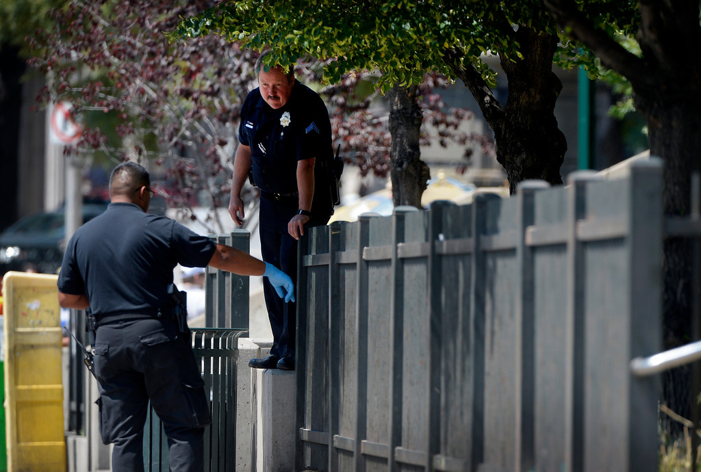 ". Authorities search a crime scene on Colfax Avenue after a shooting between Broadway and Lincoln Street near the Colorado Capitol Thursday morning in Denver, CO August 15, 2013. Three people are in custody and a gun has been recovered, no injuries were reported. Witnesses described the incident as a ""shootout\"" between two people, but police could not confirm that. (Photo By Craig F. Walker / The Denver Post)"