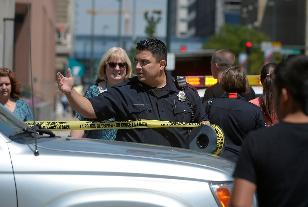 ". A Denver Police officer secures a crime scene on Colfax Avenue after a shooting between Broadway and Lincoln Street near the Colorado Capitol Thursday morning in Denver, CO August 15, 2013. Three people are in custody and a gun has been recovered, no injuries were reported. Witnesses described the incident as a ""shootout\"" between two people, but police could not confirm that. (Photo By Craig F. Walker / The Denver Post)"