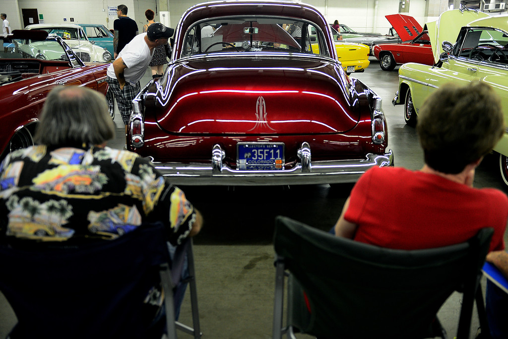 . People take in the automobiles on display during the Denver Modernism show on Sunday, August 25, 2013 at the Denver Coliseum. Spectators took in a car show as well as having the chance to shop at the exhibition hall where vendors had many mid-century items for sale. (Photo by AAron Ontiveroz/The Denver Post)