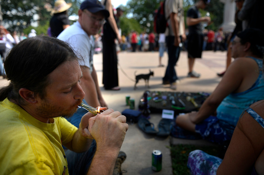 ". Jeremy Casimir lights up some wax hash watching the huge line for free marijuana joints that were handed out at Civic Center Park to any person age 21 or older at the formal launch of ""No on Proposition AA\"" Campaign, to oppose the highest tax increase in Colorado history, authorizing a 30% State tax on recreational marijuana (15% excise tax and 15% sales tax). No remuneration whatsoever was accepted for the marijuana.  Handing out free marijuana to adults 21+ is legal under the Colorado Constitution, Article XVIII Section 16 (\""Amendment 64\""). September 09, 2013 Denver, Colorado. (Photo By Joe Amon/The Denver Post)"