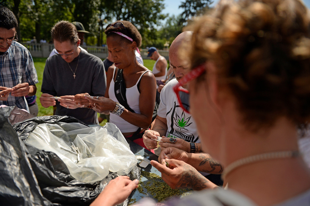. A group rolls joints to handout free during a rally at Denver Civic Center Park, September 09, 2013. The joint handout is a demonstration to oppose new tax increases on marijuana. (Photo By RJ Sangosti/The Denver Post)