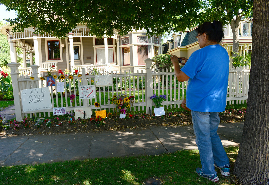 . Ruby Wildcat takes a photo of all of the cards, flowers, notes, pictures and candle left in front of the Mork and Mindy house at 1619 Pine Street in Boulder, CO on August 12, 2014 in honor to of Robin Williams who died of an apparent suicide at his home in California.   (Photo By Helen H. Richardson / The Denver Post)