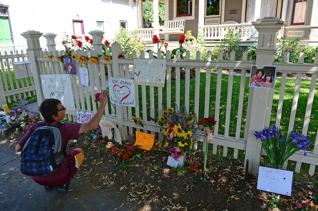 . Jason Martinez, of Superior, takes a photo of some of the notes left behind on the fence of the Mork and Mindy house at 1619 Pine Street in Boulder, CO on August 12, 2014(Photo By Helen H. Richardson / The Denver Post)