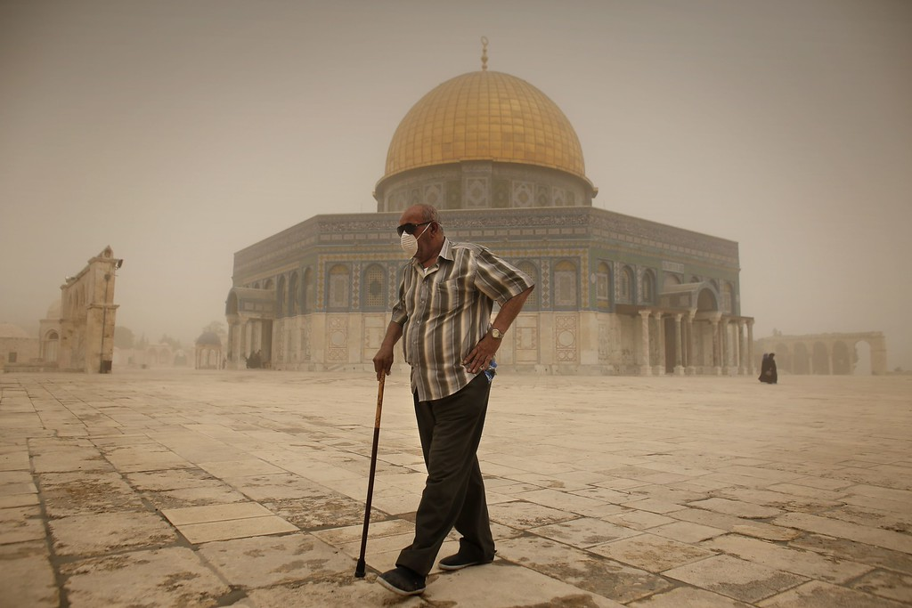 . A Palestinian man wears a mask to protect his face from the dust as he walks past the Dome of the Rock mosque in the al-Aqsa Mosque compound, during a sandstorm on September 8, 2015, in the old city of Jerusalem. A massive sandstorm has blanketed much of the Middle East. Large parts of Lebanon, Israel and Cyprus were shrounded in a thick cloud of dust that meteorologists said had swept in from Iraq and Syria.  AFP PHOTO / AHMAD GHARABLI AHMAD GHARABLI/AFP/Getty Images