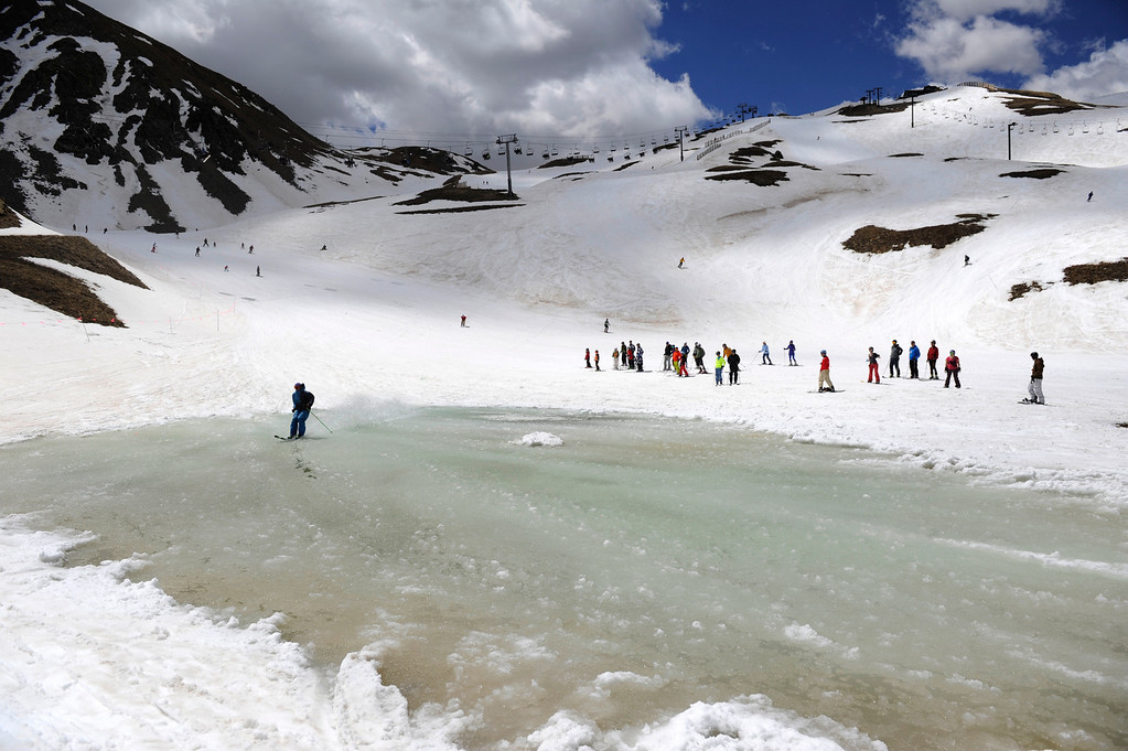 . SUMMIT COUNTY, CO - JUNE 08: A snowboarder successfully skims a natural pond that gathered with ice-cold water near the Dercum\'s Gulch area at the Arapahoe Basin ski area in Summit County Colorado, Saturday morning, June 08, 2013. Skiers and snowboarders alike challenged the pond, some making it some crashing and getting very wet. The ski area will close for the season at the end of the day, Sunday June 09, 2013.  (Photo By Andy Cross/The Denver Post)
