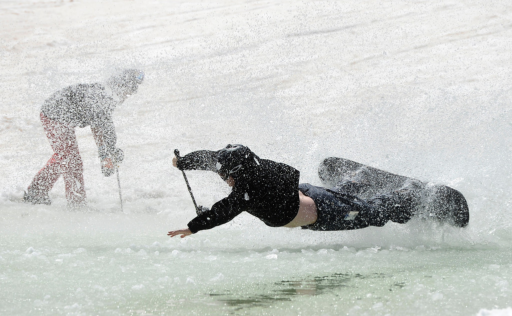 . SUMMIT COUNTY, CO - JUNE 08: Snowboarder, Kevin Christian, from Avon Colorado, tries,  unsuccessfully to skim a natural pond that gathered with ice-cold water near the Dercum\'s Gulch area at the Arapahoe Basin ski area in Summit County Colorado, Saturday morning, June 08, 2013. The ski area will close for the season at the end of the day, Sunday June 09, 2013.  (Photo By Andy Cross/The Denver Post)
