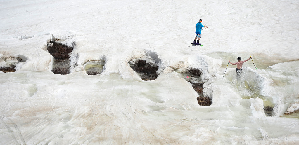 . SUMMIT COUNTY, CO - JUNE 08: A skier navigates a natural pond formed from snowmelt at the Arapahoe Basin ski area in Summit County Colorado, Saturday morning, June 08, 2013.  The ski area will close for the season at the end of the day, Sunday June 09, 2013.  (Photo By Andy Cross/The Denver Post)