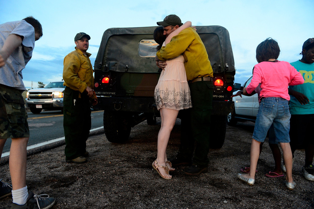 . Chris Butterfield, of the Army National Guard 1157 fire unit, hugs his wife, Julie, as he and other crews return to the incident command post during a shift change at Pine Creek High School as shifts change. Crews continued to fight the Black Forest Fire into Sunday evening as rains and cool weather set in. (Photo by AAron Ontiveroz/The Denver Post)