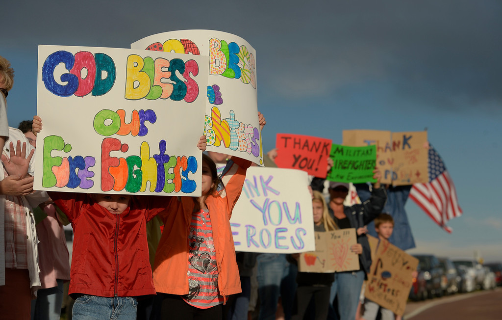 . BLACK FOREST, CO - JUNE 16:  Jackson Stone, 8 and his sister Emily, 11, hold up hand made signs with dozens of Colorado Springs and area residents who turned out at the corner of Old Ranch Road and Thunder Mountain Road outside of the Black Forest Fire Incident Command Post to cheer on firefighters and law enforcement officials as they come off of the fire line for the evening on June 16, 2013. The command post is set up at Pine Creek High School. The fire is currently 65% contained.  Photo by Helen H. Richardson/The Denver Post)