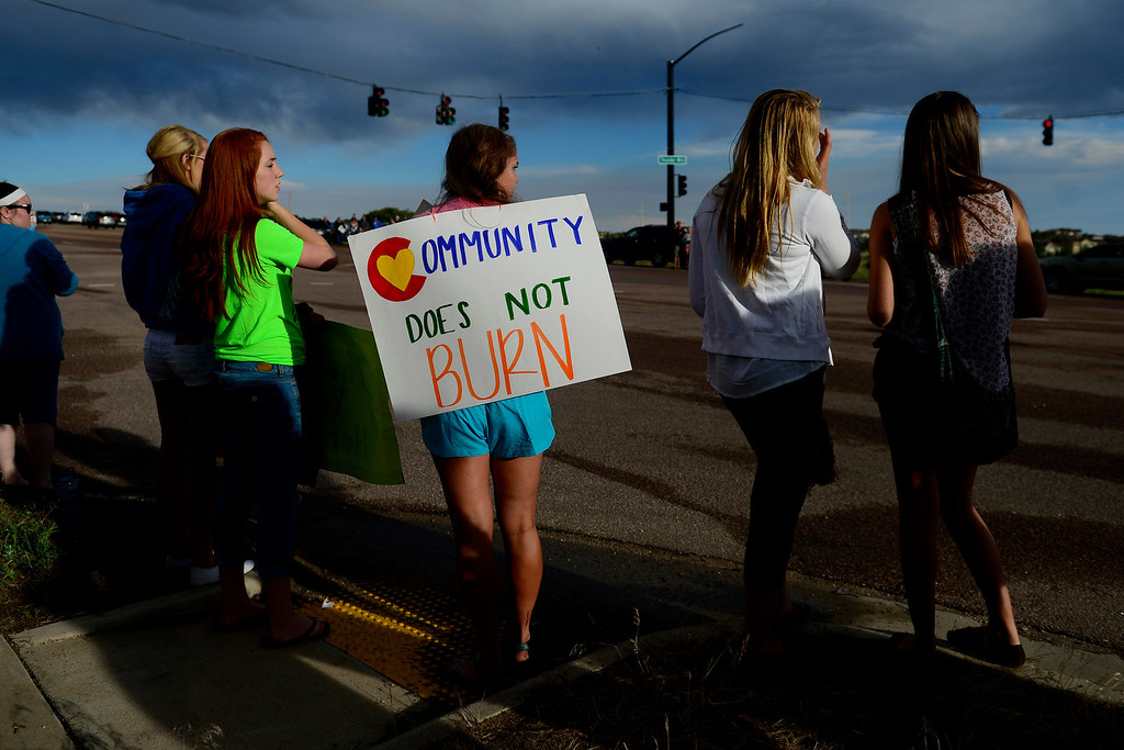 . Christina Martinez, 18, wears a pair of signs as she joins crowds in welcoming fire crews and other public officials back to the incident command post at Pine Creek High School as shifts change. Crews continued to fight the Black Forest Fire into Sunday evening as rains and cool weather set in. (Photo by AAron Ontiveroz/The Denver Post)