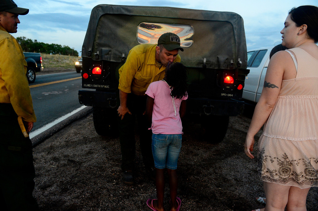 . Chris Butterfield, of the Army National Guard 1157 fire unit, kisses his daughter, Jojo, as he and other crews return to the incident command post during a shift change at Pine Creek High School as shifts change. Crews continued to fight the Black Forest Fire into Sunday evening as rains and cool weather set in. (Photo by AAron Ontiveroz/The Denver Post)