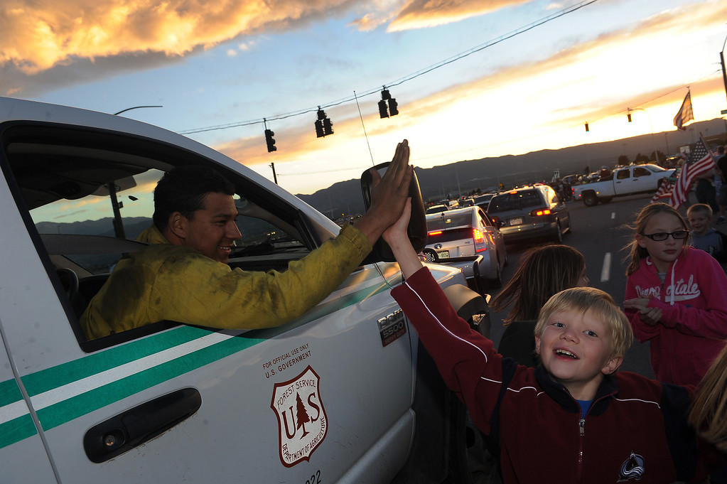 . BLACK FOREST, CO - JUNE 16:  US Forest service firefighter Wilber Vasquez gets a high five from a Colorado Spring resident.  Hundreds of Colorado Springs and area residents turned out at the corner of Old Ranch Road and Thunder Mountain Road outside of the Black Forest Fire Incident Command Post to cheer on firefighters and law enforcement officials as they come off of the fire line for the evening on June 16, 2013. The command post is set up at Pine Creek High School. The fire is currently 65% contained.  Photo by Helen H. Richardson/The Denver Post)