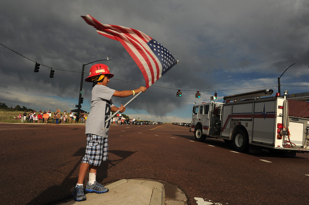 . BLACK FOREST, CO - JUNE 16:  Landen Epperson, 10, of Colorado Springs, CO holds up a large American flag as he and dozens of other area residents turned out at the corner of Old Ranch Road and Thunder Mountain Road outside of the Black Forest Fire Incident Command Post to cheer on firefighters and law enforcement officials as they come off of the fire line for the evening on June 16, 2013. The command post is set up at Pine Creek High School. The fire is currently 65% contained.  Photo by Helen H. Richardson/The Denver Post)