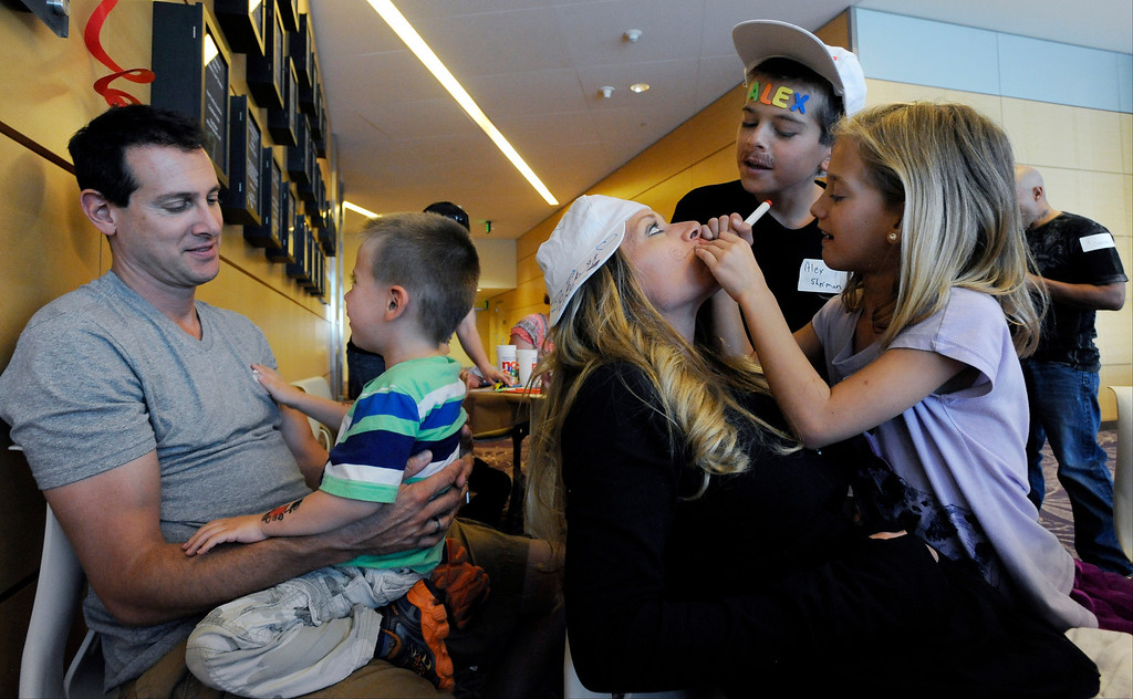 """. Jon Sherman, left, and his wife Kim, center, spend time with their four kids (three shown) during Children\'s Hospital Colorado\'s \""""Take Me Out to the Ballgame\"""" cancer survivor\'s event on June 23, National Cancer Survivors\' Day, at the Children\'s Hospital in Aurora, Colo. Alex, 11, a twin, second from right, was diagnosed with a type of lymphoma, and has been in remission for over a year. Photo by Jamie Cotten, Special to The Denver Post"""