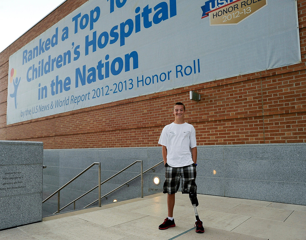 """. Garrison Hayes, 14, poses on a balcony during Children\'s Hospital Colorado\'s \""""Take Me Out to the Ballgame\"""" cancer survivor\'s event on June 23, National Cancer Survivors\' Day, at the Children\'s Hospital in Aurora, Colo. Hayes was diagnosed with a type of sarcoma (cancer of soft tissue, connective tissue or bone) when he was six-years old, and after a surgery that substituted his ankle for his knee, is cancer free and plans to partake in paralympics in the near future. Photo by Jamie Cotten, Special to The Denver Post"""