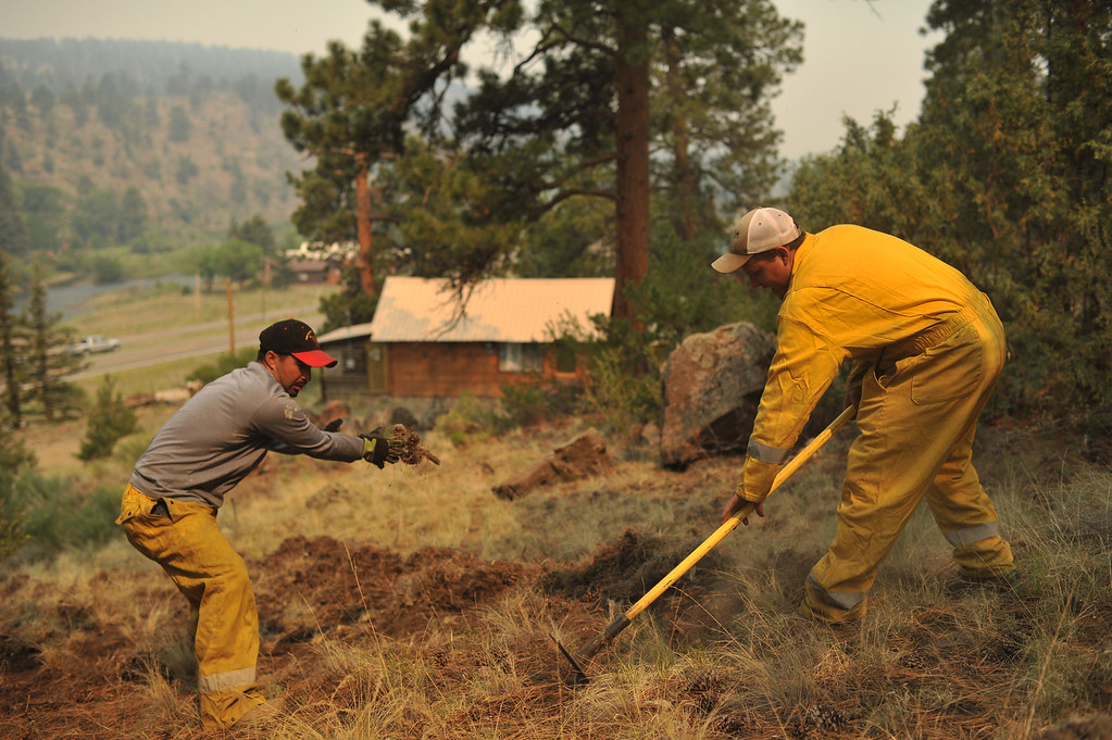 . Michael Abeyta, left, and Mark Sowards from South Conejos fire department are moving grass for fire mitigation at Masonic Park area in South Fork. (Photo By Hyoung Chang/The Denver Post)