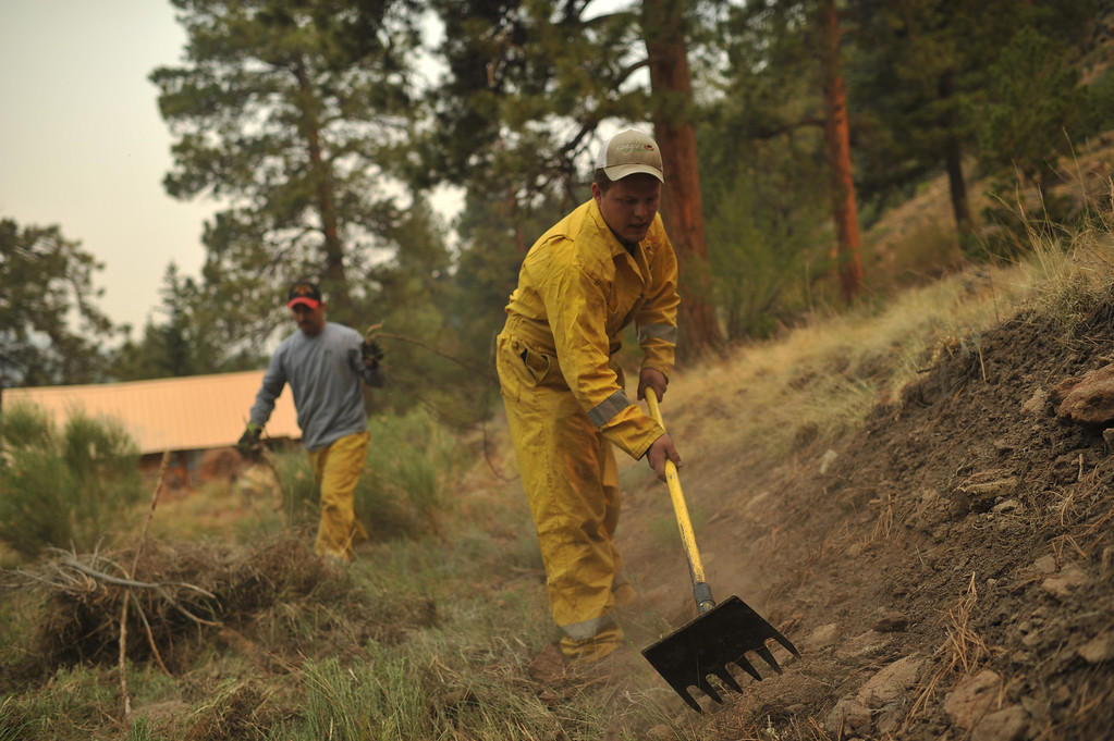 . Michael Abeyta, left, and Mark Sowards from South Conejos fire department are moving the grass for fire mitigation at Masonic Park area in South Fork. (Photo By Hyoung Chang/The Denver Post)