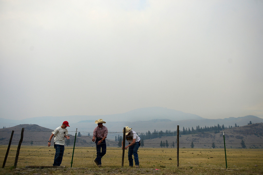 . Wranglers from left to right Dalton Davidson, Chris (no last name) and Dusty Weller fix a fence as the air is filled with a smoky haze from the West Fork Fire burning near Creede. The West Fork Fire grew to more than 70,000 acres overnight. (Photo by AAron Ontiveroz/The Denver Post)