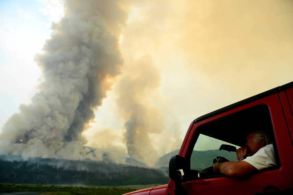 . Jay Vaughn, a summer resident of Creede, watches as the Papoose fire kicks up late in the afternoon. The three fires that make up the West Fork Complex fire now top out at more than 80 thousand acres. (Photo by AAron Ontiveroz/The Denver Post)