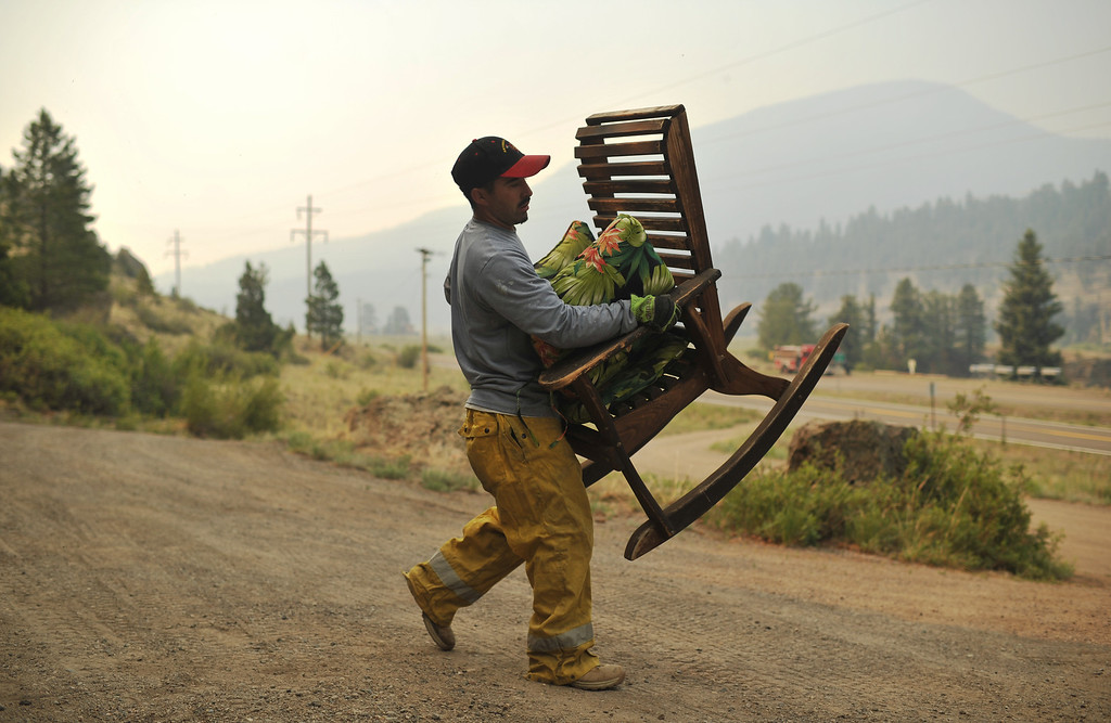 . Michael Abeyta from South Conejos fire department moves a chair from a property while doing fire mitigation at Masonic Park area in South Fork.   (Photo By Hyoung Chang/The Denver Post)