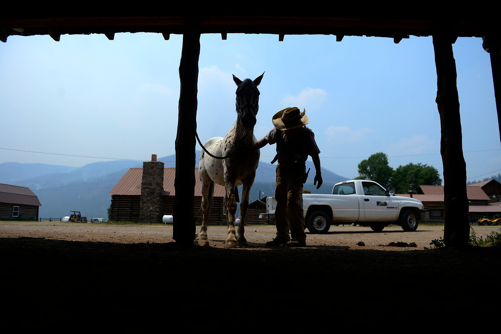 . Kirk Ellison brushes Smitty, while preparing to return more than 20 horses to their pasture across Highway 149 as the Papoose fire continues to burn near Creede. The three fires that make up the West Fork Complex fire now top out at more than 80 thousand acres. (Photo by AAron Ontiveroz/The Denver Post)