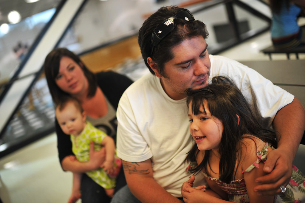 . West Fork Complex fire evacuee Sam Salazar holds his daughter Grace, 6, while his wife Colette sits nearby with their 9-month-old son Payton at Del Norte High School Gym on Friday, June 21, 2013. (Photo By Hyoung Chang/The Denver Post)