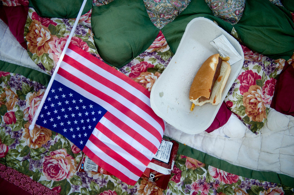 . DENVER - JULY 3: A half-eaten hotdog and an American flag lie on an abandoned quilt at Civic Center Park in Denver on July 3, 2013. (Photo By Grant Hindsley/The Denver Post)