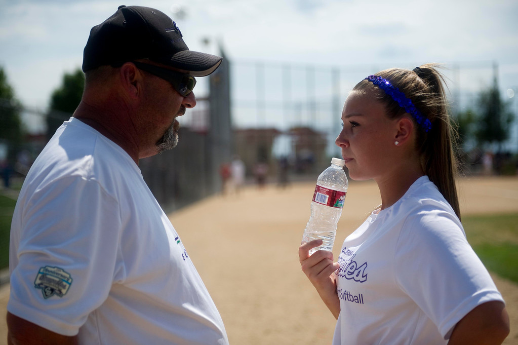 . AURORA, Co. - JULY 4: Coach Todd Clark of the California Grapettes talks with Tayler Munoz, #5, about college prospects during the Colorado Fireworks 2013 softball tournament on July 4, 2013 at Aurora Sports Park. (Photo By Grant Hindsley/The Denver Post)