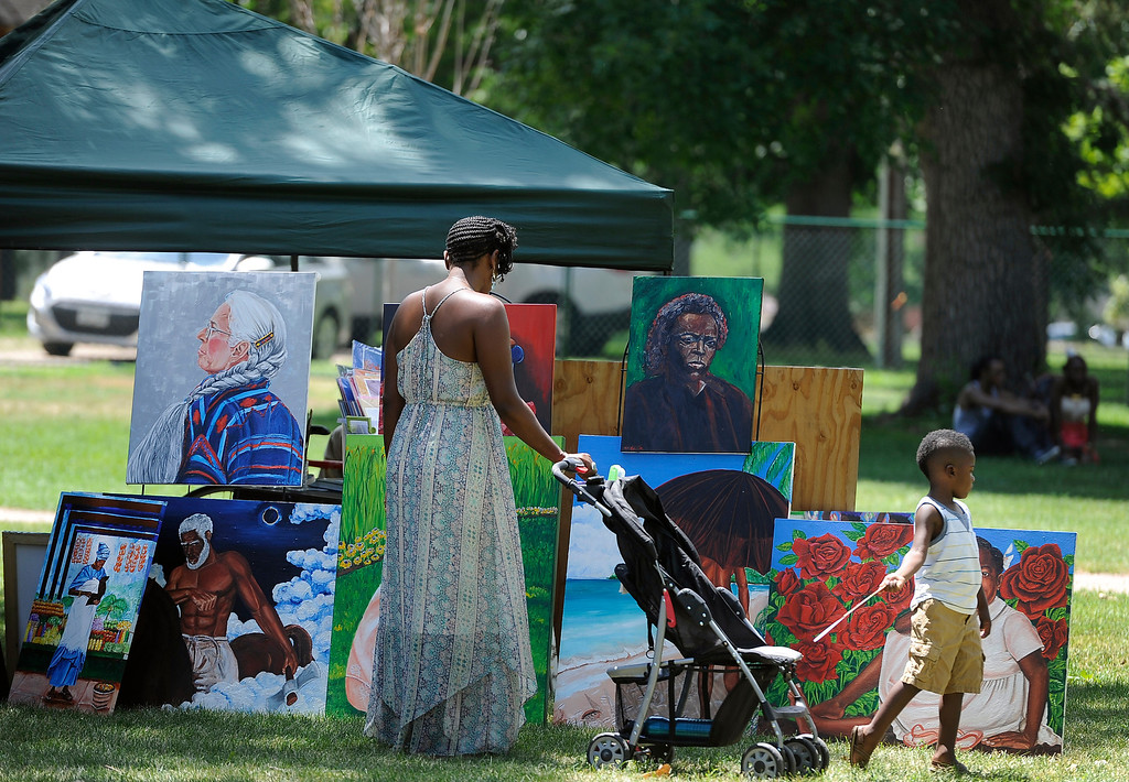 """. DENVER, CO - JULY13: Visitors view some of the work by artist Azizi Abdalla. The 27th Annual Colorado Black Arts Festival takes place in City Park with this year\'s theme \""""African American Style: an American Legacy. The festival continues through Sunday with dozens of artists, vendors, and performances taking place. (Photo By Kathryn Scott Osler/The Denver Post)"""