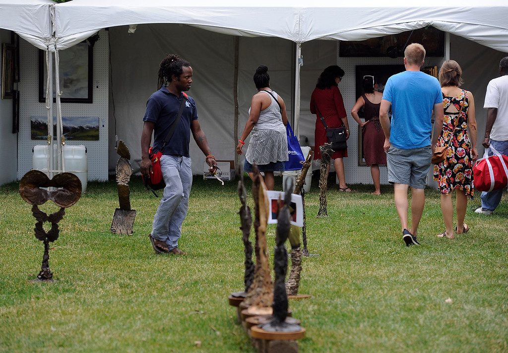 """. DENVER, CO - JULY13: Visitors walk through the sculpture garden inside the Visual Arts Pavilion. The 27th Annual Colorado Black Arts Festival takes place in City Park with this year\'s theme \""""African American Style: an American Legacy. The festival continues through Sunday with dozens of artists, vendors, and performances taking place. (Photo By Kathryn Scott Osler/The Denver Post)"""